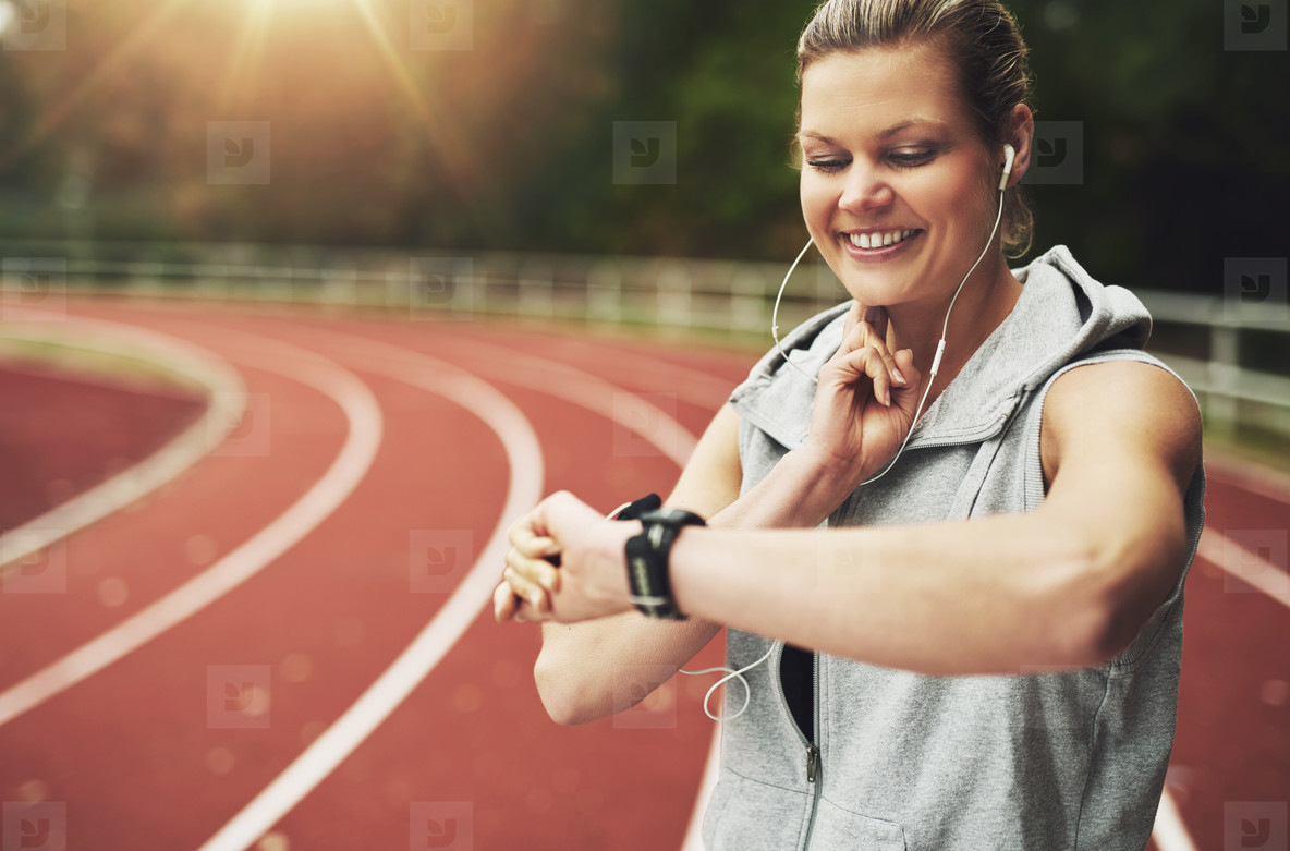 Athletic young woman looking at her watch while listening to music