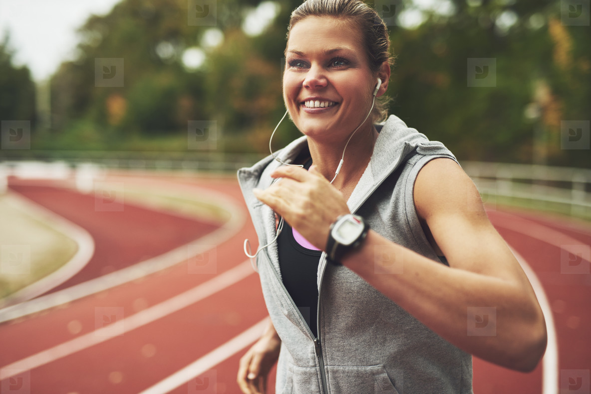 Young smiling woman running on stadium
