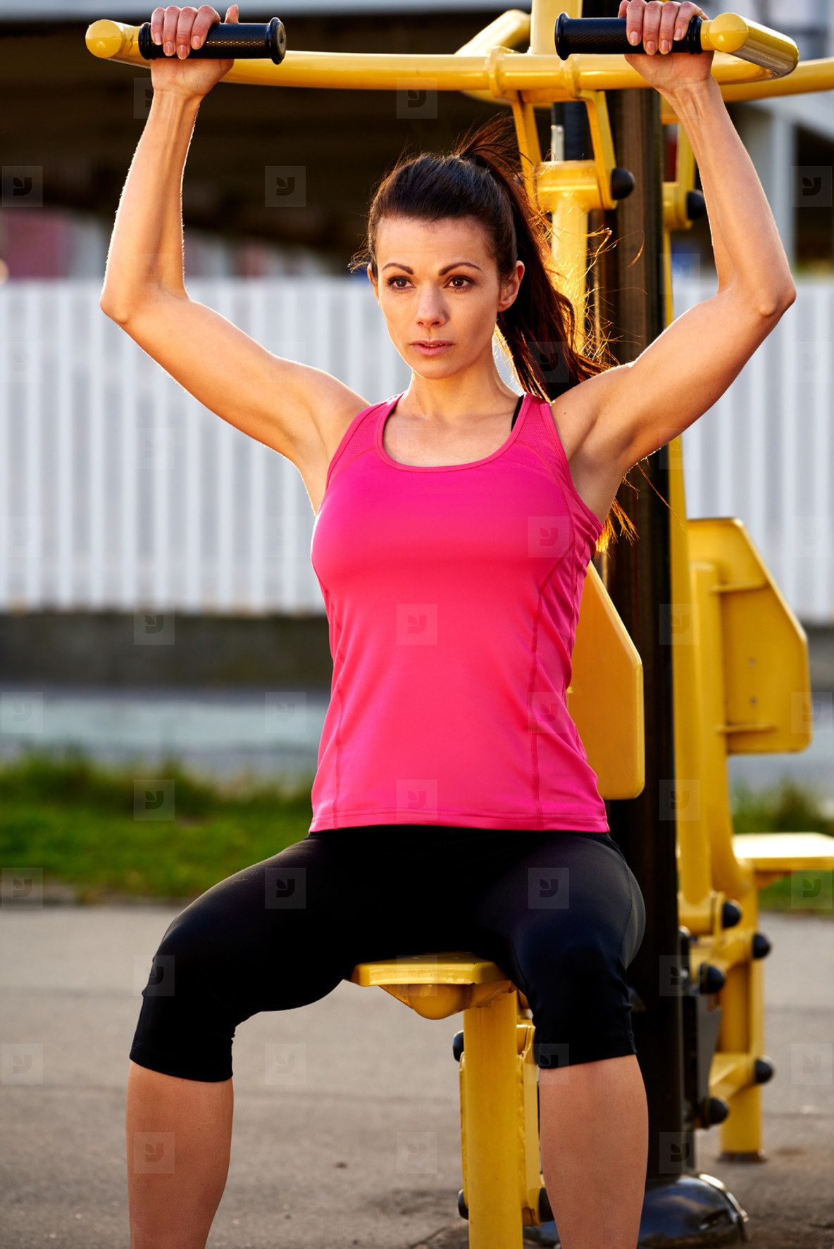 Muscular woman sitting on weights machine exercising arms
