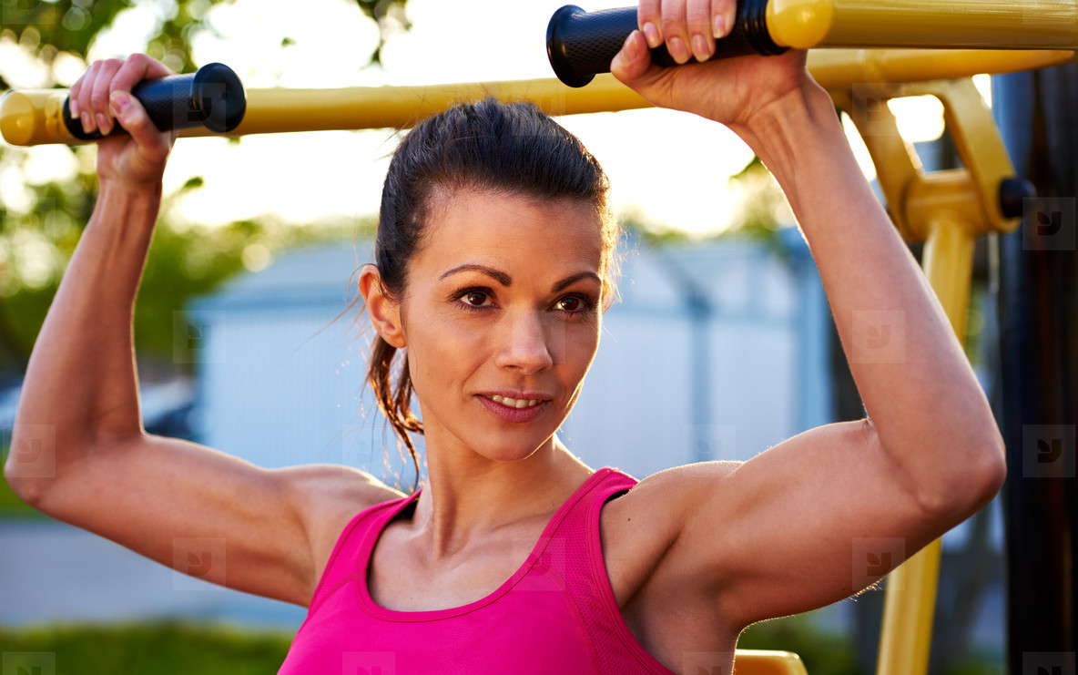 Woman smiling while lifting weights