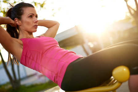 Woman sitting on bench outside doing situps
