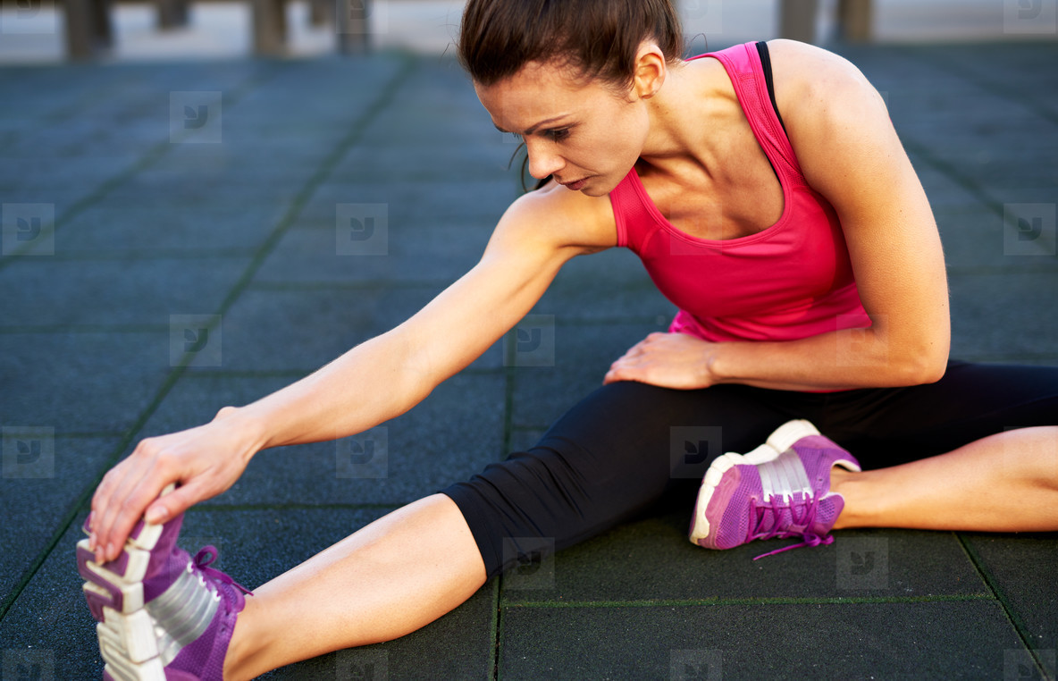 Woman on floor stretching her leg