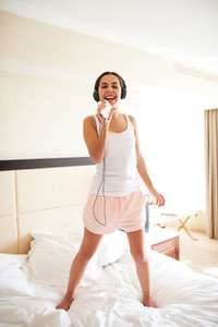 Woman standing on bed wearing headphones