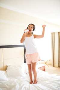 Woman standing on bed listening to headphones