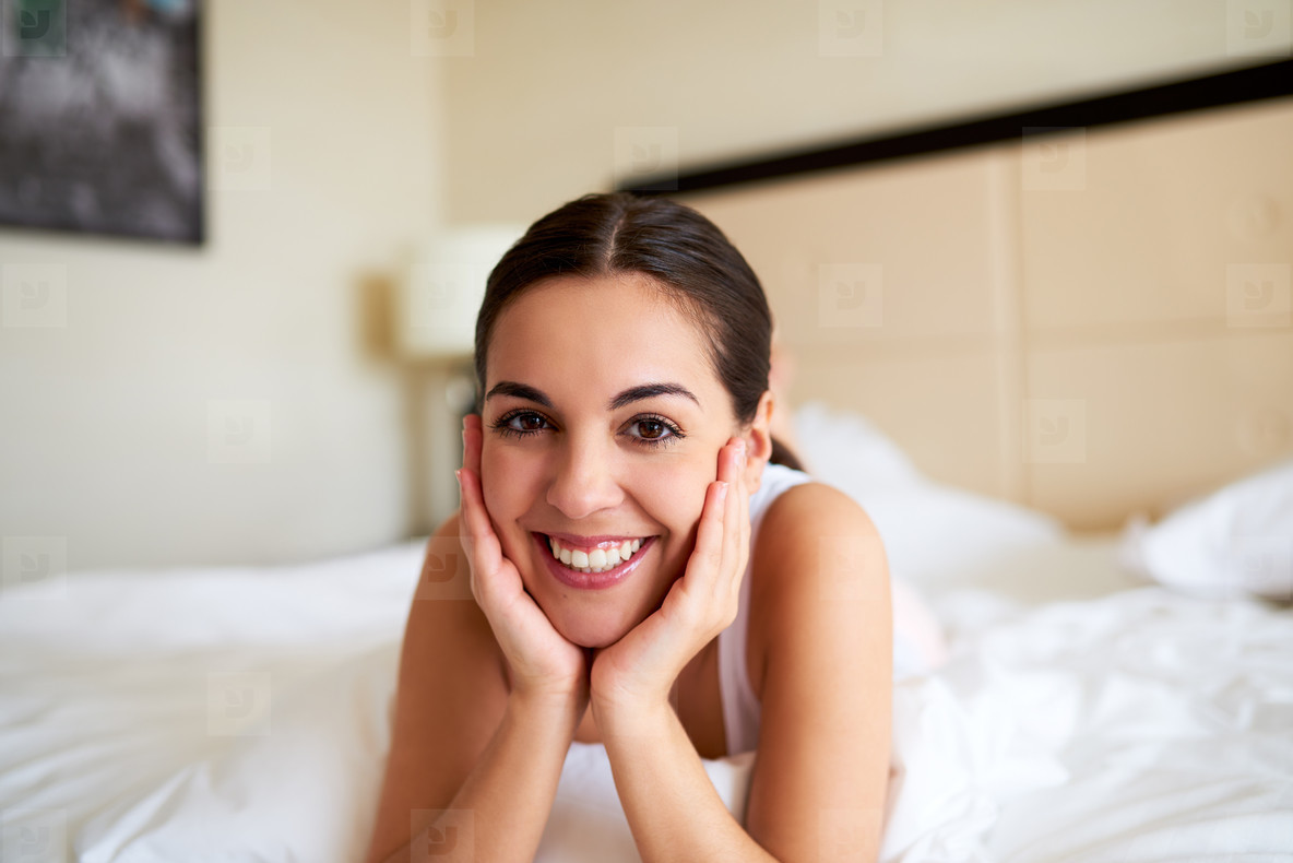 Woman lying in bed resting chin in hands
