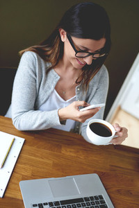 Woman smiling while checking phone and drinking coffee