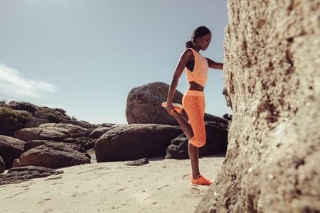 African woman stretching her legs at beach