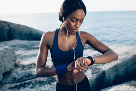 Runner checking fitness progress on her smartwatch