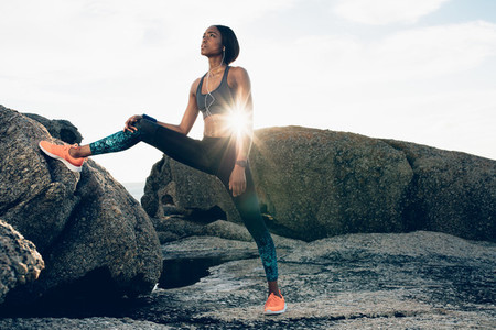 Fitness african woman standing by rock