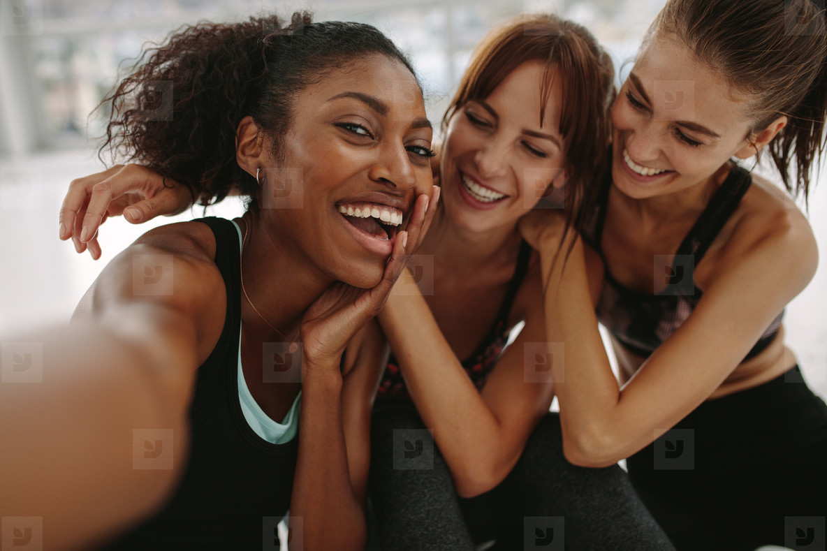 Friends talking self portrait in fitness studio