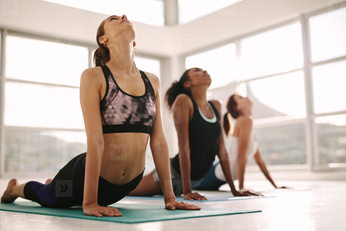 Women practicing yoga in fitness studio