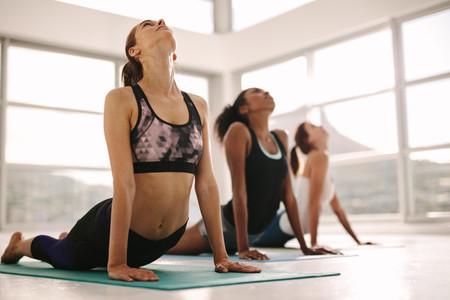 Women practicing yoga in fitness studio