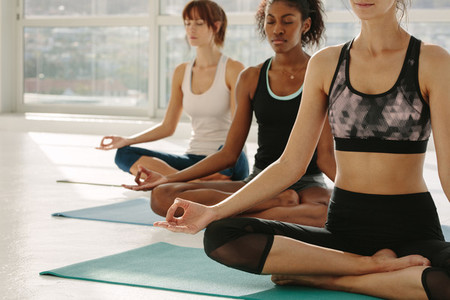 Women meditating in lotus pose at fitness studio