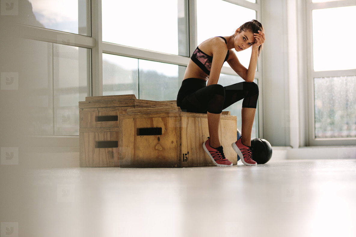 Exhausted fitness woman resting at gym