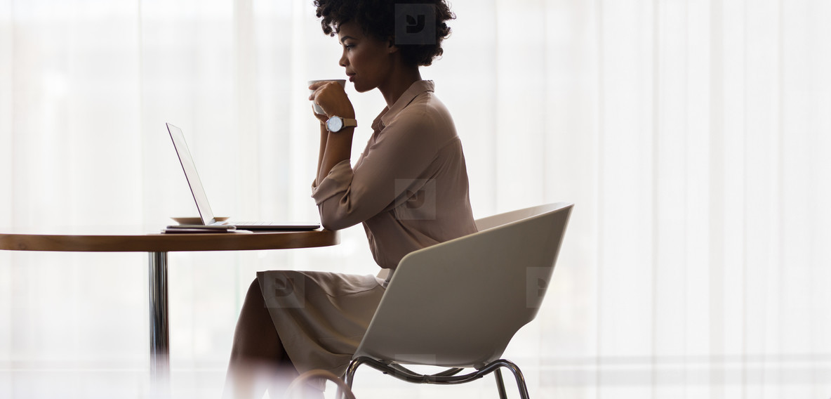 Businesswoman drinking coffee and looking at laptop