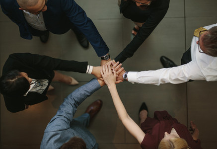 Business team putting hands together at the office