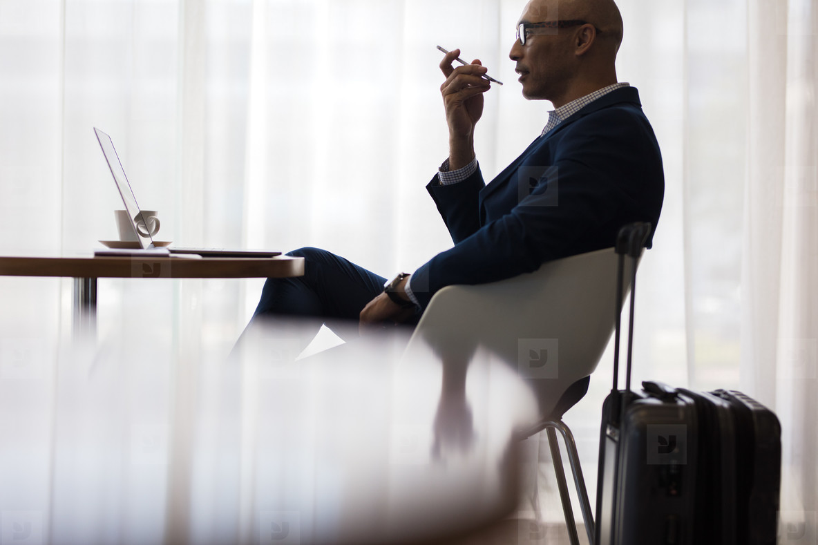 Businessman speaking on mobile phone at airport lounge