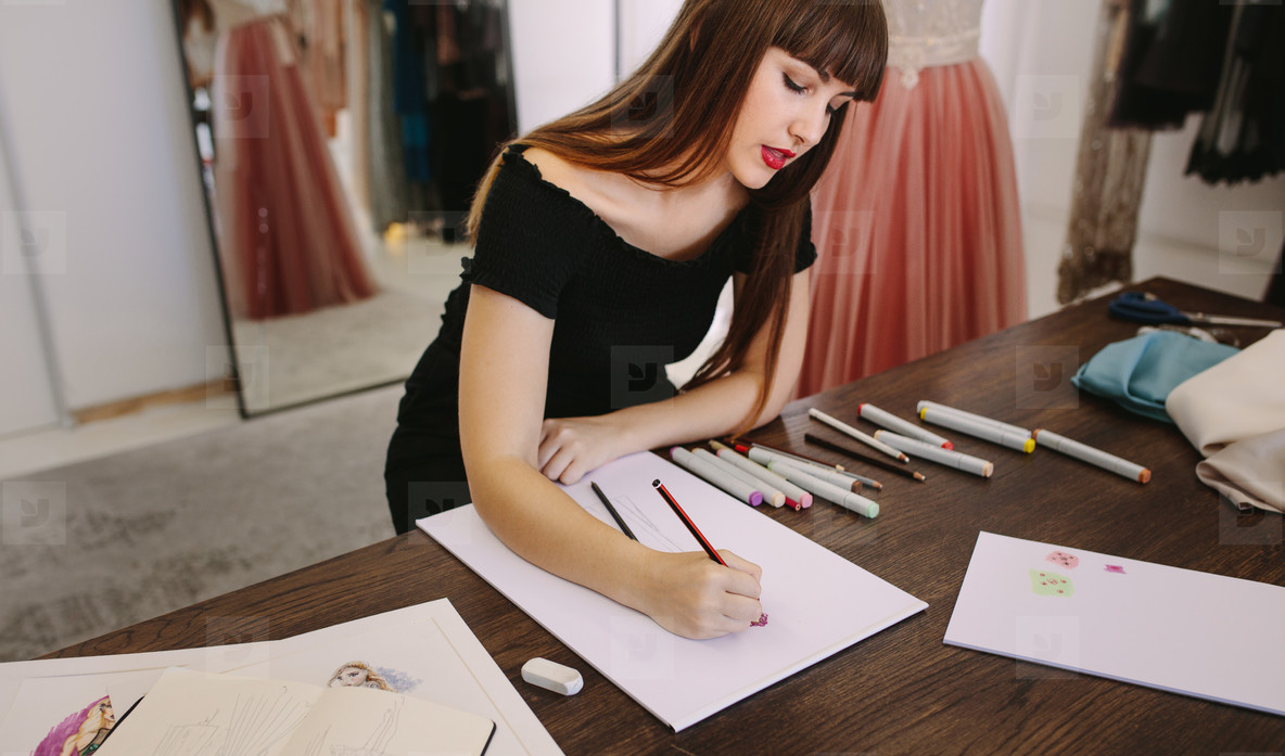 Fashion designer working on her designs in her studio