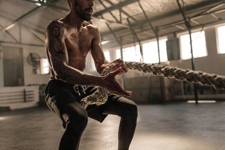 Athletic man with great physique pulling rope