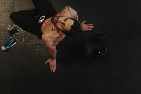 Exhausted man relaxing on gym floor after workout
