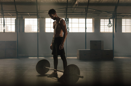 Man exercising with barbell at gym