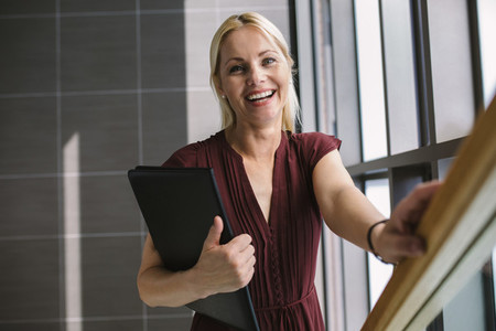 Businesswoman walking up on the stairs in office