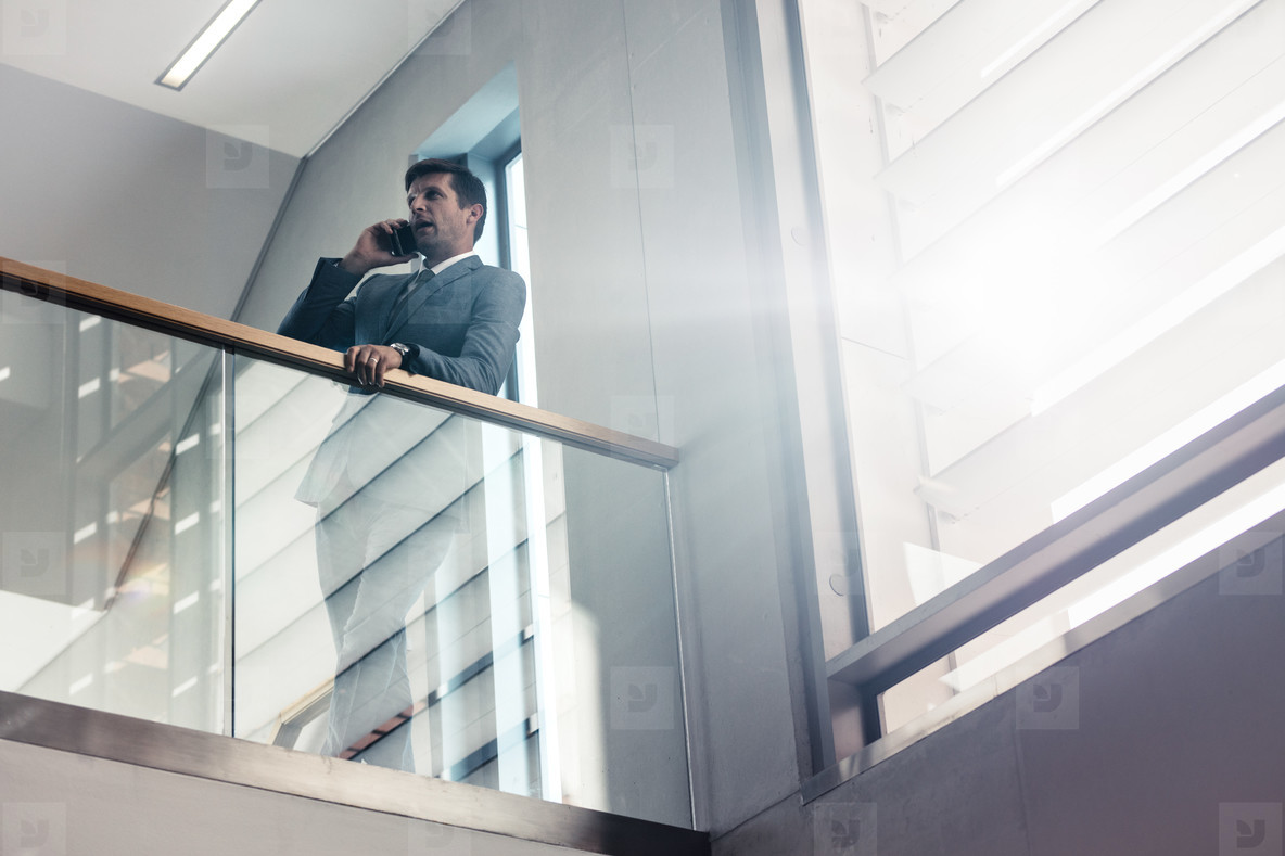 Businessman in office corridor talking on cell phone