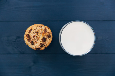 Chocolate chip cookies and glass of milk on dark background