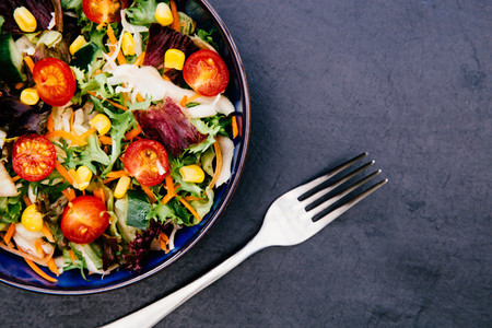 Bowl of fresh mixed salad with fork on dark background