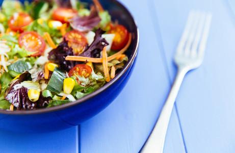 Bowl of fresh salad on blue wood table