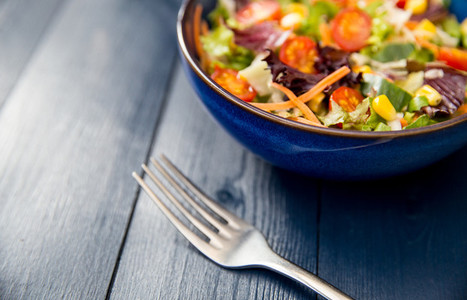 Healthy bowl of fresh salad on blue wood table