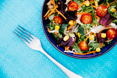 Bowl of fresh salad on bright blue background