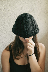 long haired girl covering her face with her hat