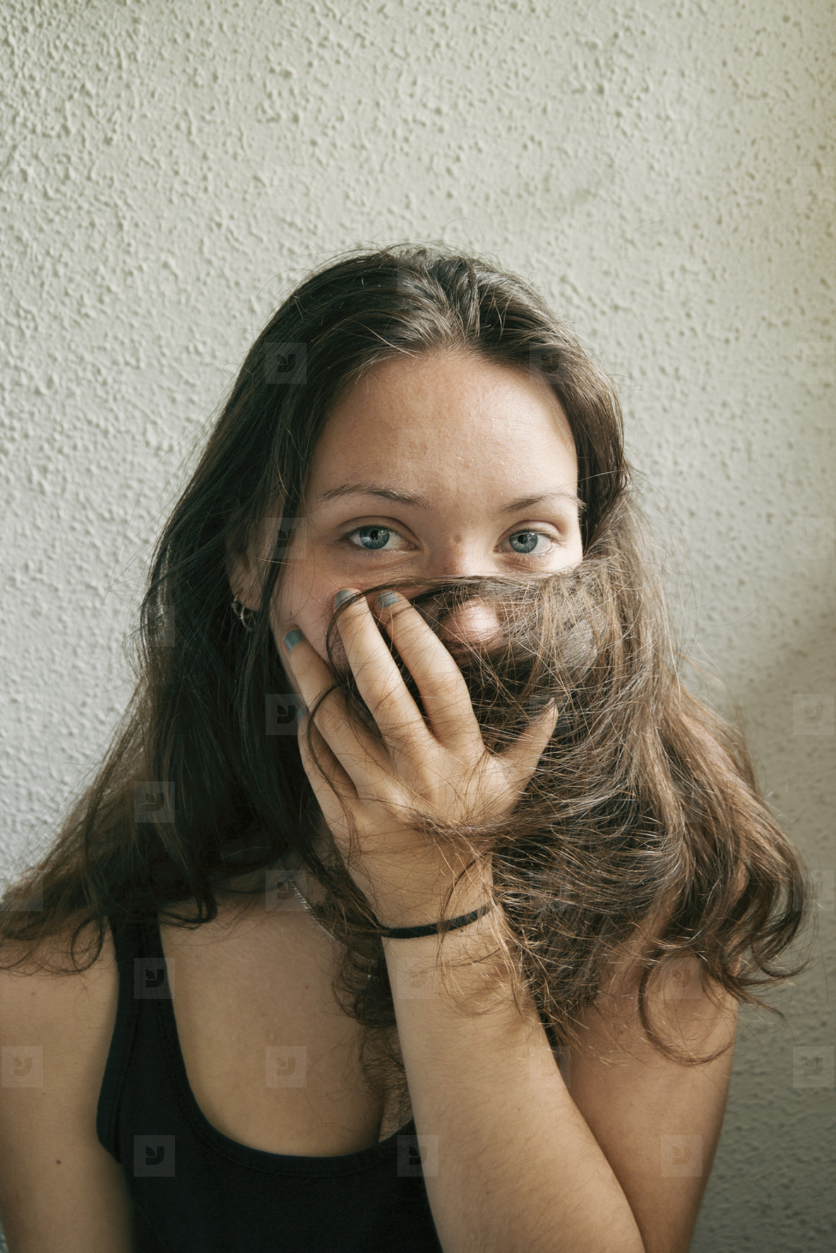 Long haired girl with blue eyes covering her hair