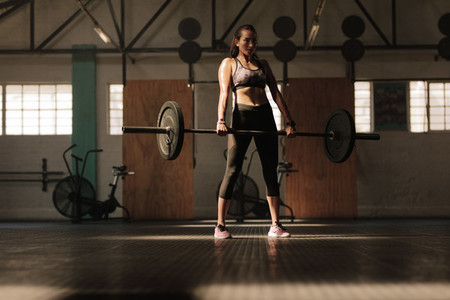 Fitness model performing weight exercise at gym