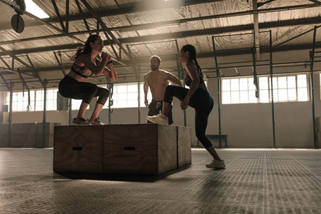 Group of people doing box jumping workout in gym