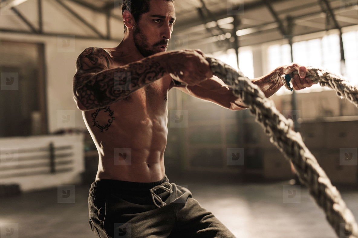 Athlete working out with battle ropes at gym