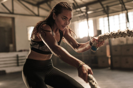 Fitness woman using battle ropes for exercising