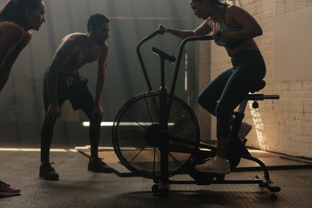 Fitness woman doing spinning at gym with trainers