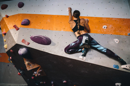 Woman climbing indoor boulder wall