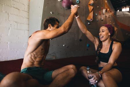 Rock climbers celebrating at a wall climbing gym