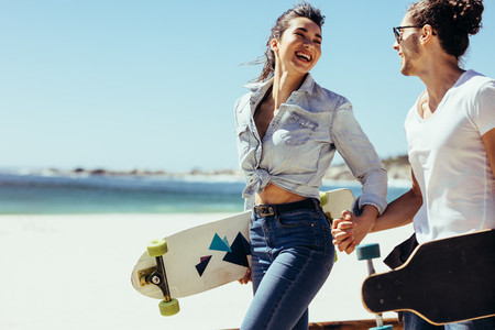Smiling couple together at the beach with skateboards