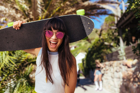 Smiling woman walking outdoors holding skateboard