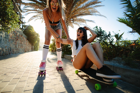 Female friends having fun with skating on summer vacation