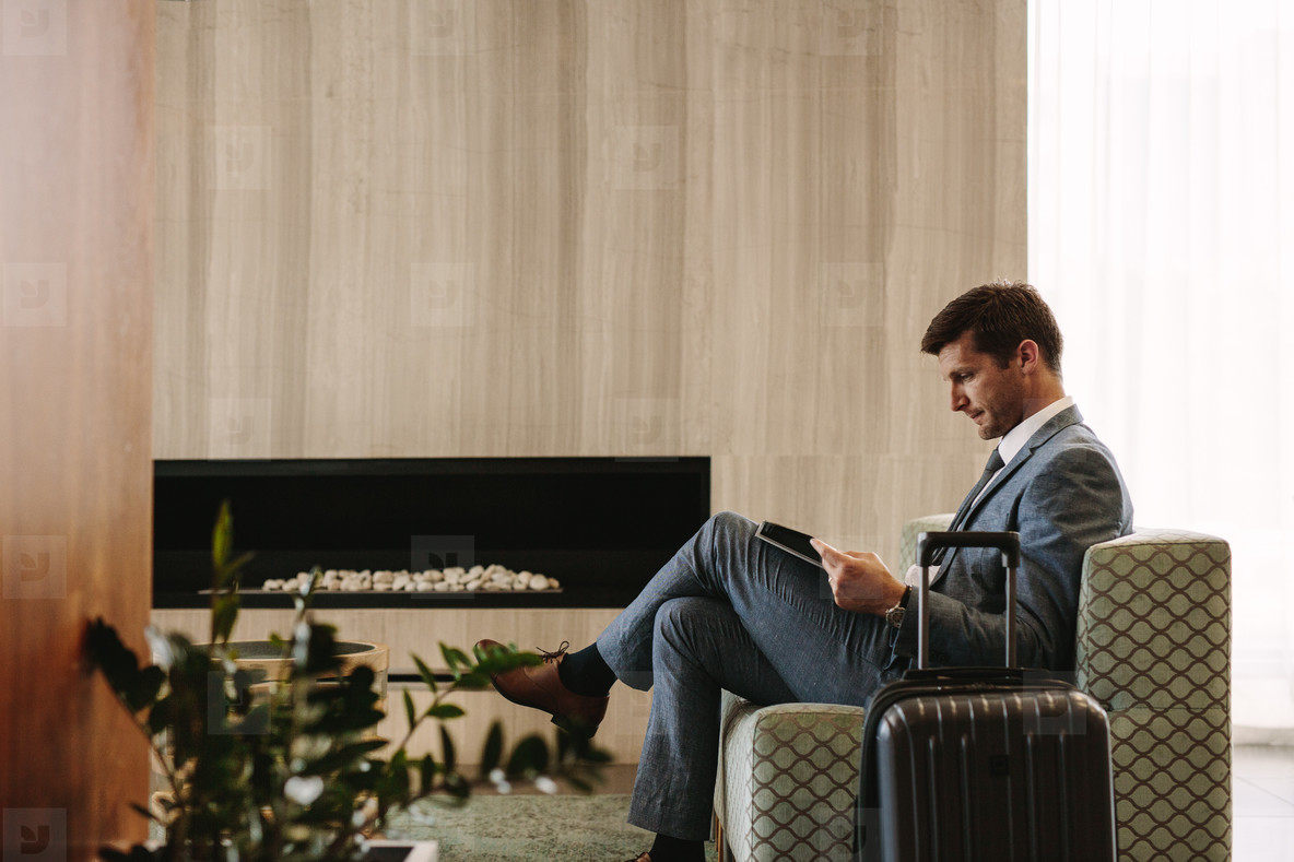 Businessman reading a magazine while waiting for his flight