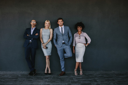 Diverse business team standing together against a wall