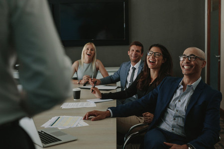 Business people laughing during a conference meeting