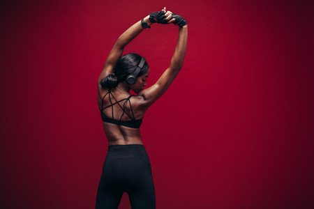 Female athlete with headphones stretching her arms