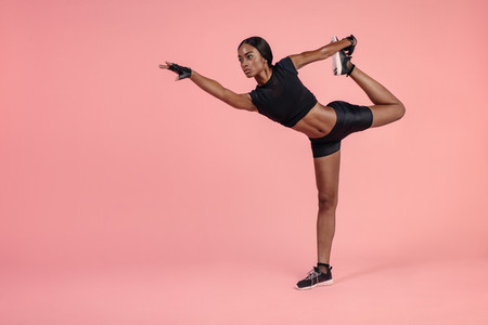 African woman practicing Natarajasana yoga pose