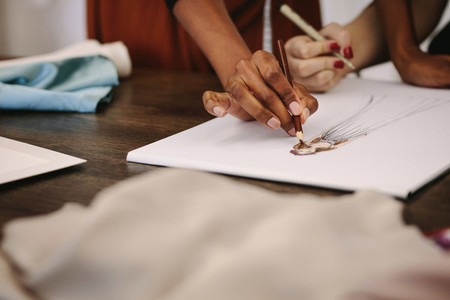 Woman fashion designers making designs on drawing paper